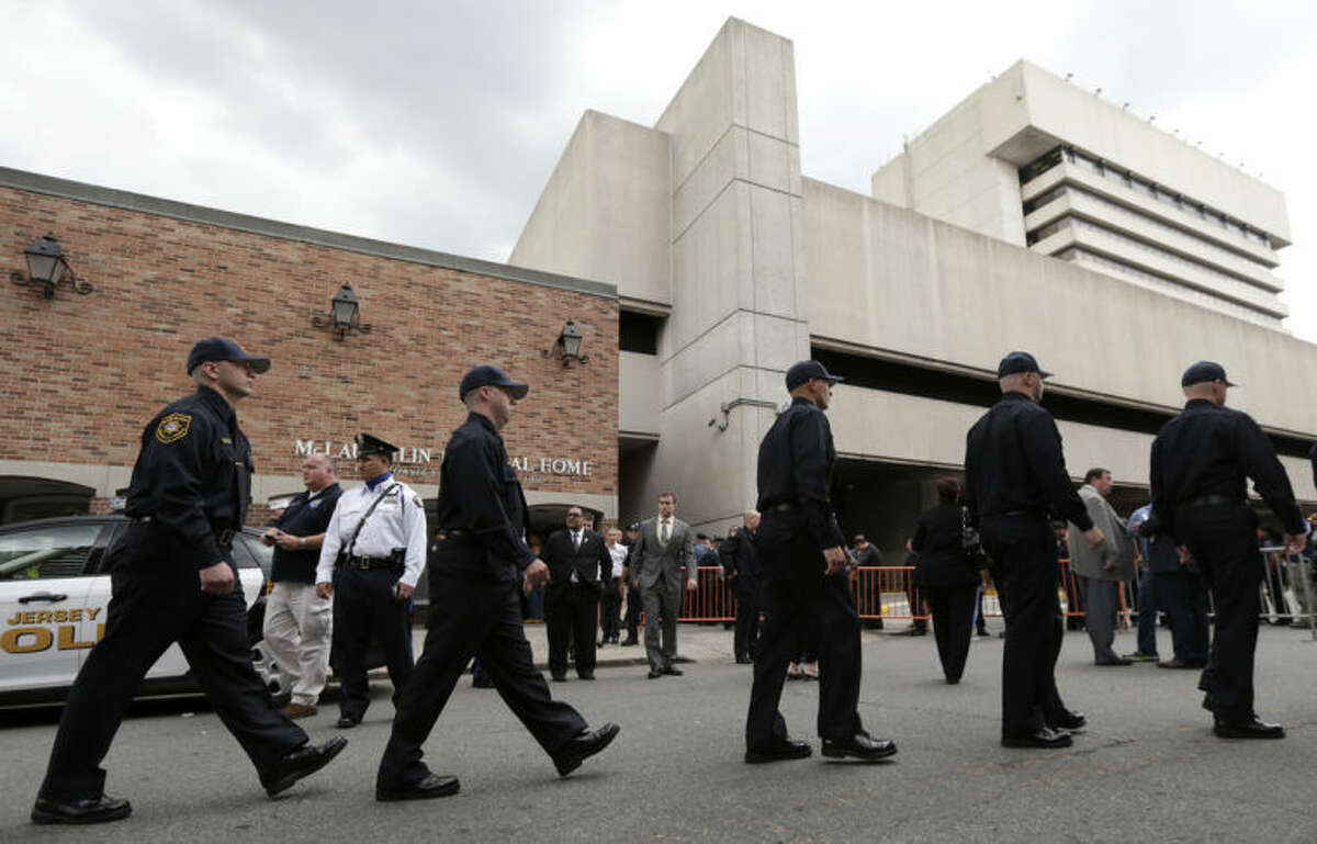 Police cadets march in a line as they arrive at McLaughlin Funeral Home during visitation hours for Jersey City Police Department officer Melvin Santiago, who was killed Sunday, July 13 while on duty, Thursday, July 17, 2014, in Jersey City, N.J. The officer was shot in the head while still in his police vehicle as he and his partner responded to an armed robbery call at a pharmacy. (AP Photo/Julio Cortez)