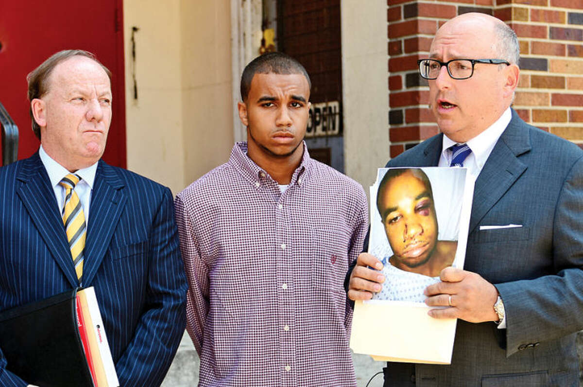 Hour photo / Erik Trautmann Attorneys Todd Haase and Phil Russell announce lawsuit for Norwalk police brutality victim Cody Greene, center, during a press conference on South Main Street Friday.