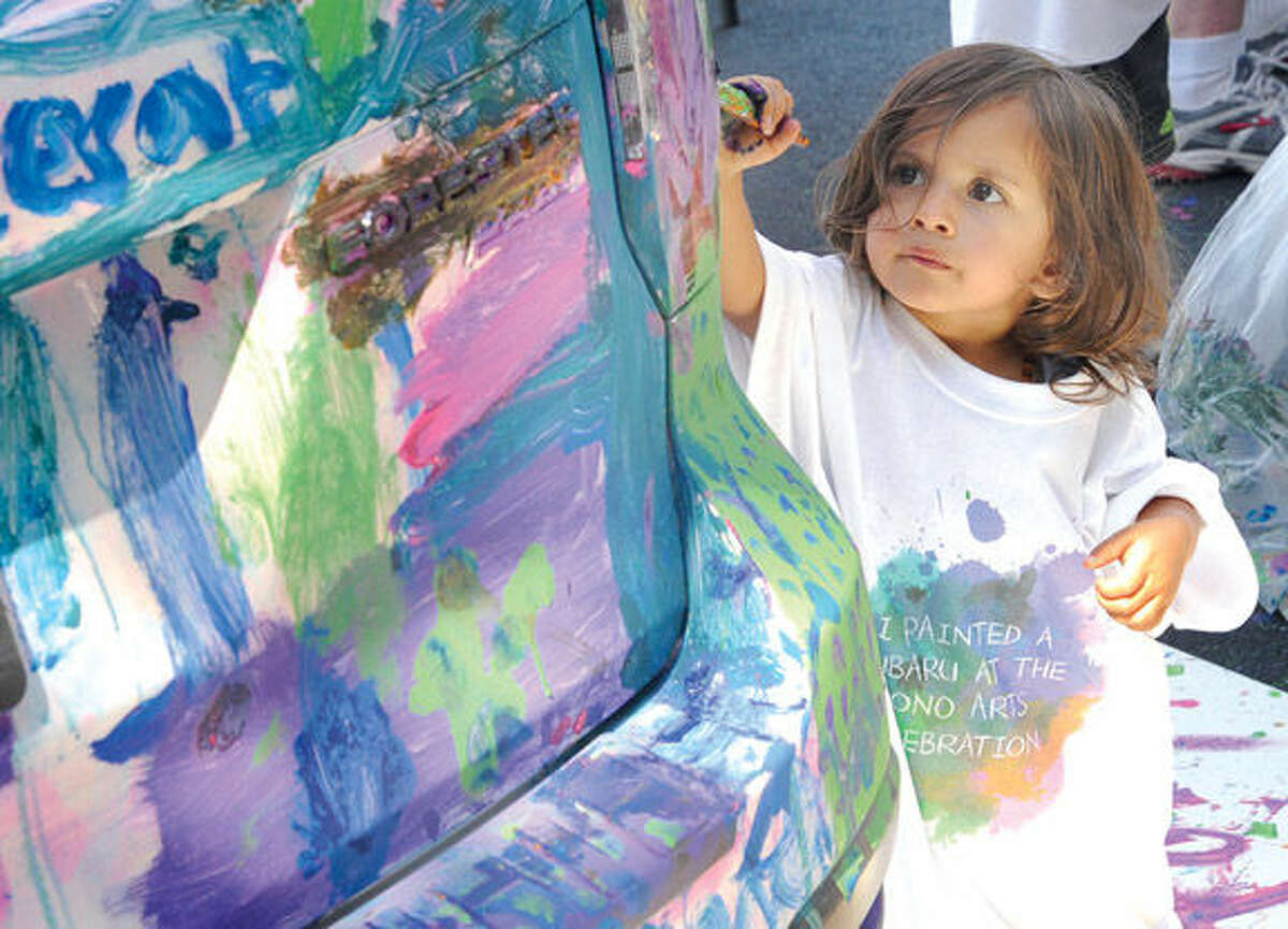 Cariad Samy 2, paints a donated car from Garavel Auto Group Sunday at the SoNo Arts Festival. Hour photo/Matthew Vinci