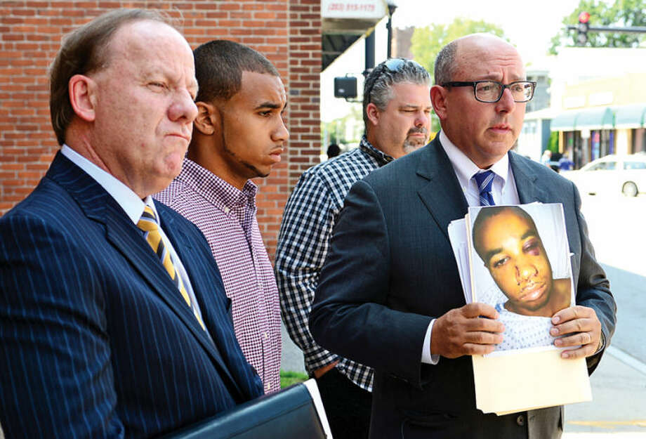 Hour photo / Erik Trautmann Attorneys Todd Haase and Phil Russell and private investigator William Smith announce lawsuit for Norwalk police brutality victim Cody Greene, second from left, during a press conference on South Main Street Friday.