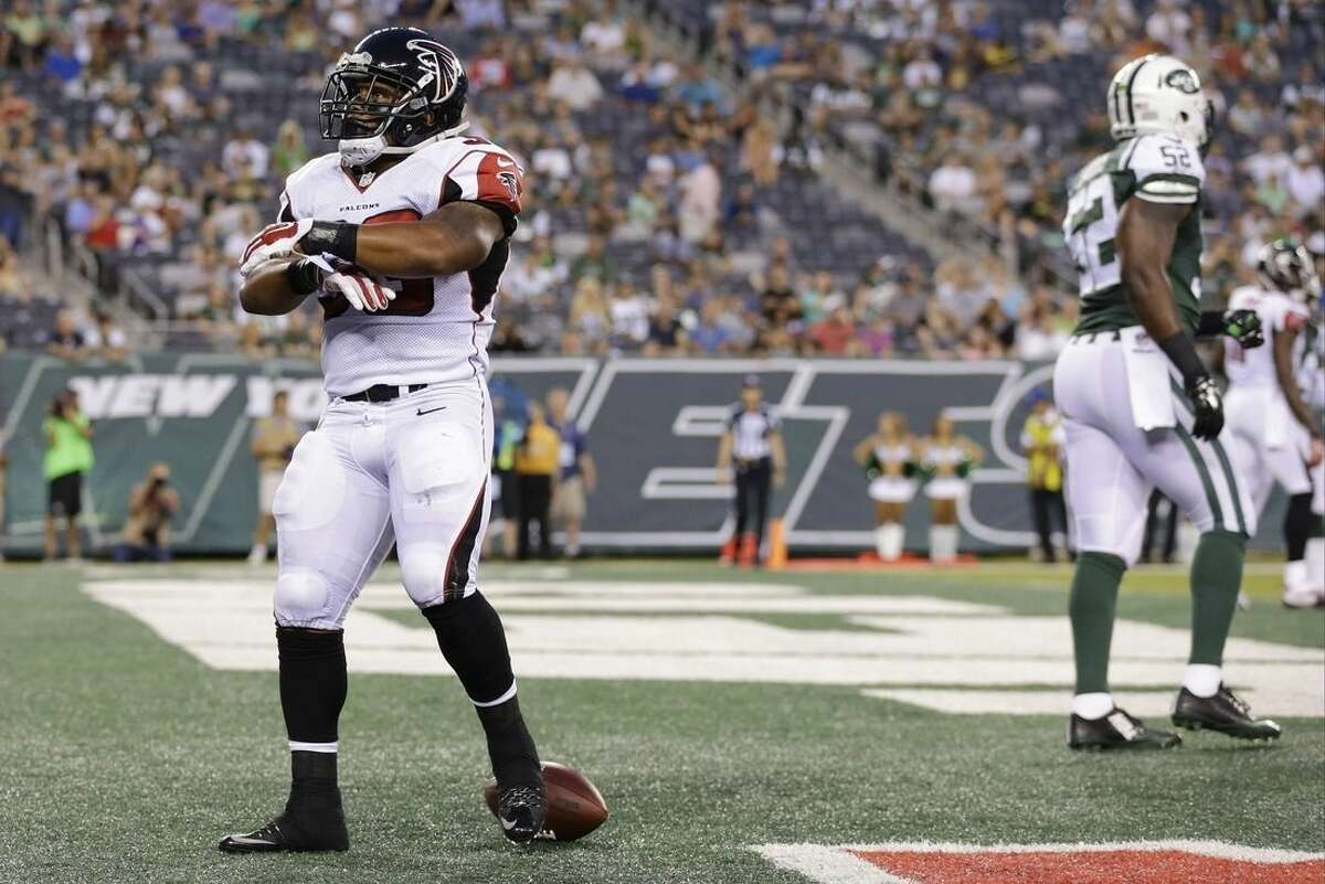 Atlanta Falcons running back Terron Ward (33) celebrates after rushing for a touchdown as New York Jets' David Harris (52) walks away during the first half of a preseason NFL football game Friday, Aug. 21, 2015, in East Rutherford, N.J. (AP Photo/Adam Hunger)