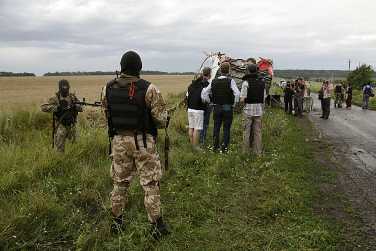 Pro-Russia fighters sedure the area as the OSCE (Organization for Security and Co-operation in Europe) delegation, at centre, arrives at the crash site of a Malaysia Airlines jet near the village of Hrabove, eastern Ukraine, Friday, July 18, 2014. Representatives from OSCE and four Ukrainian experts have traveled into rebel-controlled areas to begin an investigation into the downing of the Malaysia Airlines plane on Wednesday and the deaths of all its passengers and crew. (AP Photo/Dmitry Lovetsky)