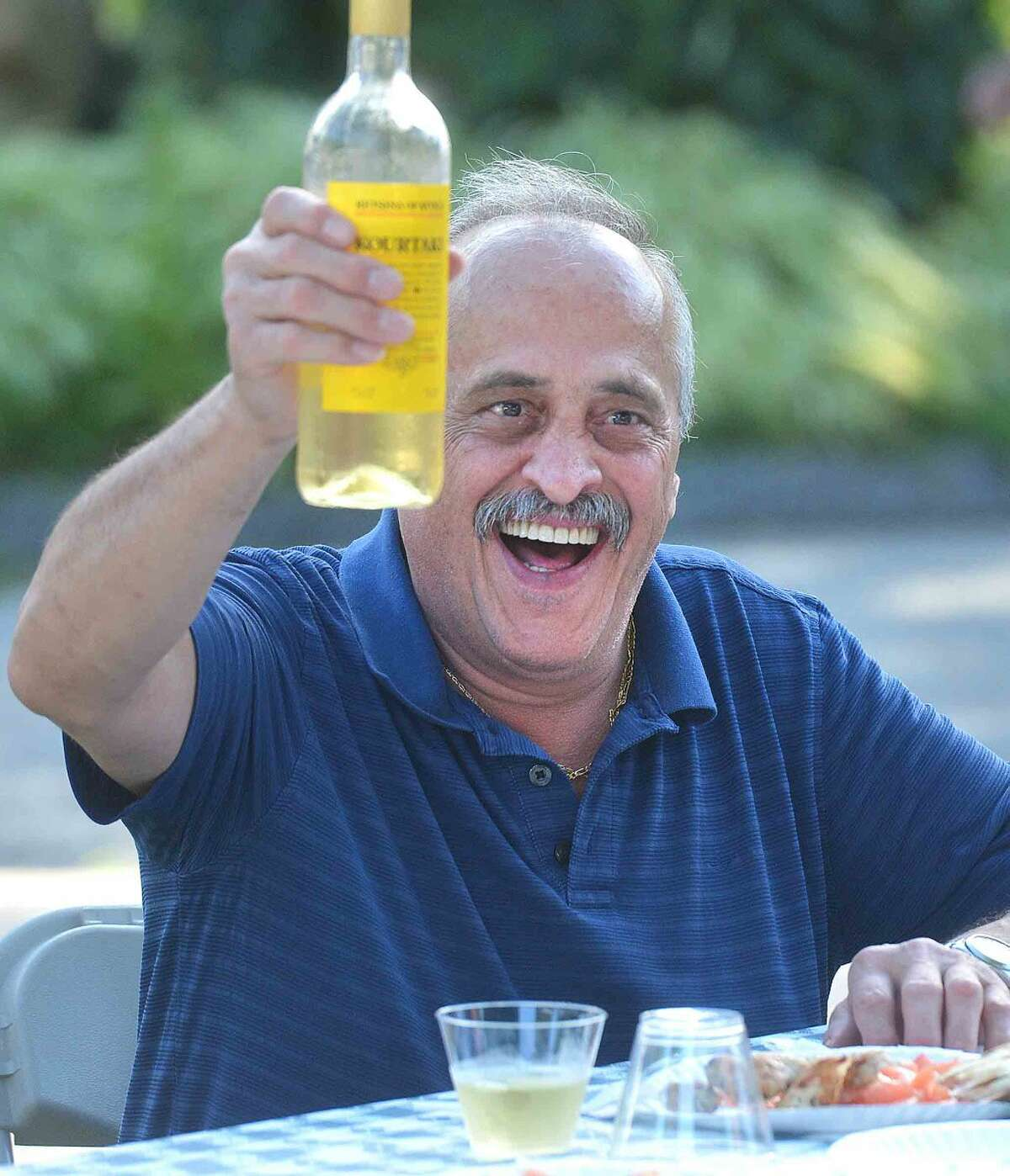 Hour Photo/Alex von Kleydorff Jimmy Iosisides enjoys some greek Retsina with freinds and family at the 2015 Norwalk Greek Festival at St George Greek Orthodox Church