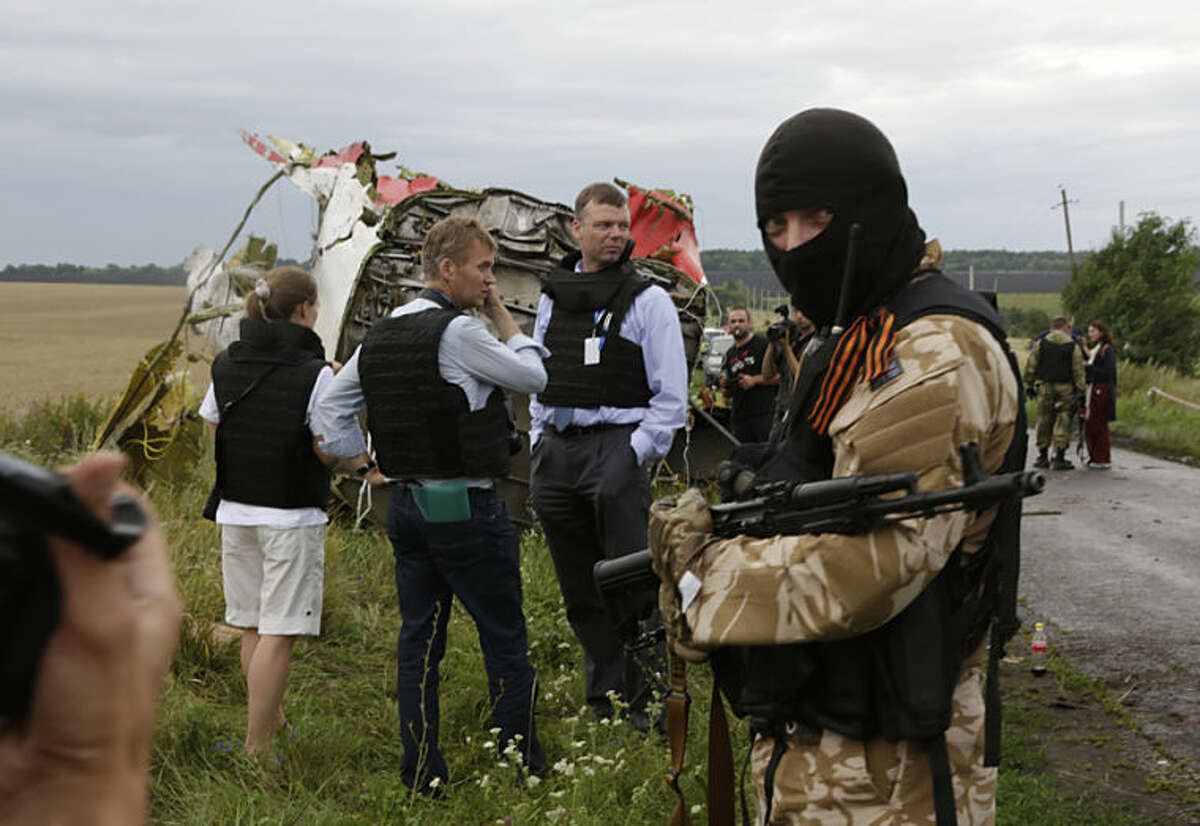 Representatives from the OSCE (Organization for Security and Co-operation in Europe) delegation arrive, centre, as Pro-Russia fighters provide security, at the crash site of a Malaysia Airlines passenger jet near the village of Hrabove, eastern Ukraine, Friday, July 18, 2014. Representatives from OSCE and four Ukrainian experts have traveled into rebel-controlled areas to begin an investigation into the downing of the Malaysia Airlines plane on Wednesday and the deaths of all its passengers and crew. (AP Photo/Dmitry Lovetsky)