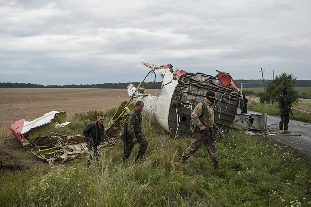 Pro-Russian fighters at the crash site of a Malaysia Airlines passenger jet near the village of Hrabove, Ukraine, Friday, July 18, 2014. Representatives of the OSCE (Organization for Security and Co-operation in Europe) delegation have arrived at the crash site with four Ukrainian experts to begin an investigation into the downing of the Malaysia Airlines plane on Thursday and the deaths of all its passengers and crew. (AP Photo/Evgeniy Maloletka)