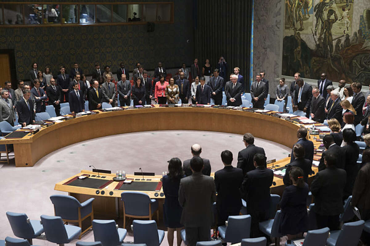 Members of the U.N. Security Council stand for a moment of silence for the lives lost on Malaysia Airlines Flight 17 on Thursday during a meeting at United Nations headquarters, Friday, July 18, 2014. Britain's U.N. Mission says it requested an emergency meeting after Thursday's downing of a Malaysia Airlines plane carrying 298 people over eastern Ukraine. (AP Photo/John Minchillo)