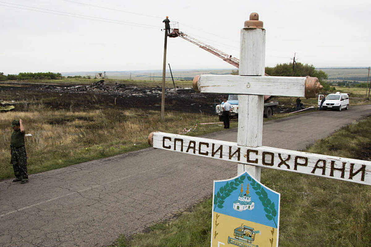 """A Ukrainian electrical worker repairs a power line at the site of the crashed Malaysia Airlines passenger plane near the village of Rozsypne, Ukraine, eastern Ukraine Friday, July 18, 2014, with an Orthodox cross in the foreground, words are reading """"Save and Protect"""". Rescue workers, policemen and even off-duty coal miners were combing a sprawling area in eastern Ukraine near the Russian border where the Malaysian plane ended up in burning pieces Thursday, killing all 298 aboard. (AP Photo/Dmitry Lovetsky)"""
