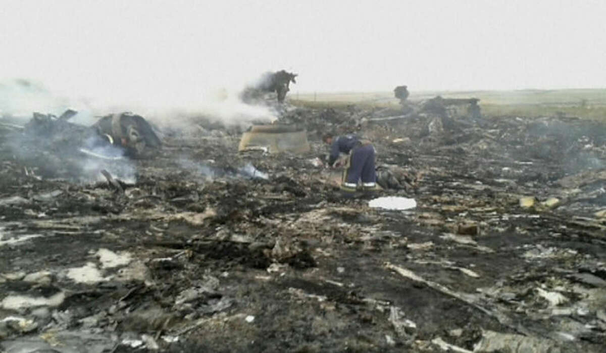 In this image taken from video, Thursday July 17, 2014, people walk amongst the debris at the crash site after a passenger plan was shot down Thursday as it flew over Ukraine, near the village of Hrabove, in eastern Ukraine. Malaysia Airlines tweeted that it lost contact with one of its flights as it was traveling from Amsterdam to Kuala Lumpur over Ukrainian airspace. (AP Photo/Channel 1) RUSSIA OUT - TV OUT