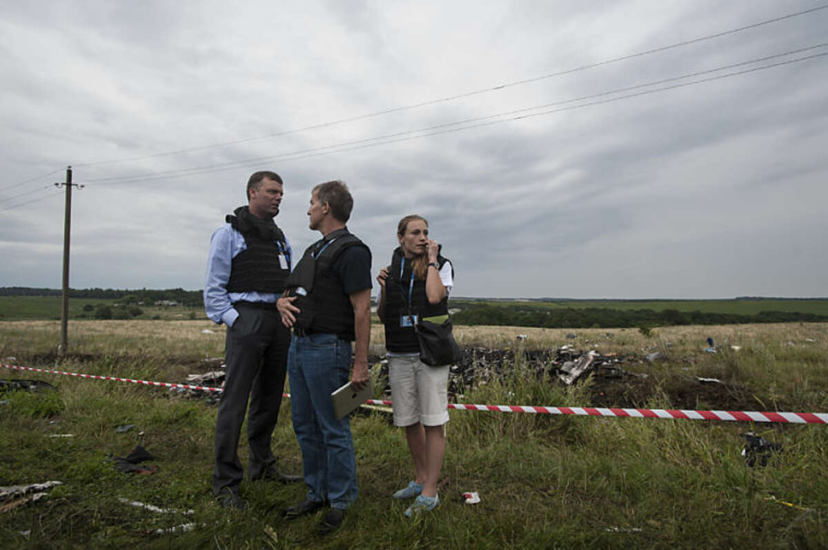 Alexander Hug, left, deputy head of the OSCE mission, stands at the crash site of a Malaysia Airlines jet near the village of Hrabove, eastern Ukraine, Friday, July 18, 2014. Representatives from the Organization for Security and Cooperation in Europe and four Ukrainian experts had traveled into rebel-controlled areas to begin an investigation into the attack that killed 298 people from nearly a dozen nations. The militia allowed them to look at part of the crash site, but refused to let them view the area where the engines came down. (AP Photo/Evgeniy Maloletka)