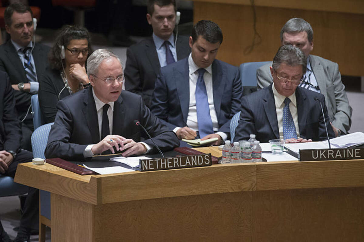 Netherlands U.N. Ambassador Karel van Oosterom, left, speaks alongside Ukrainian U.N. Ambassador Yuriy Sergeyev, right, during a U.N. Security Council meeting at United Nations headquarters, Friday, July 18, 2014. Britain's U.N. Mission says it requested an emergency meeting after Thursday's downing of a Malaysia Airlines plane carrying 298 people over eastern Ukraine. (AP Photo/John Minchillo)