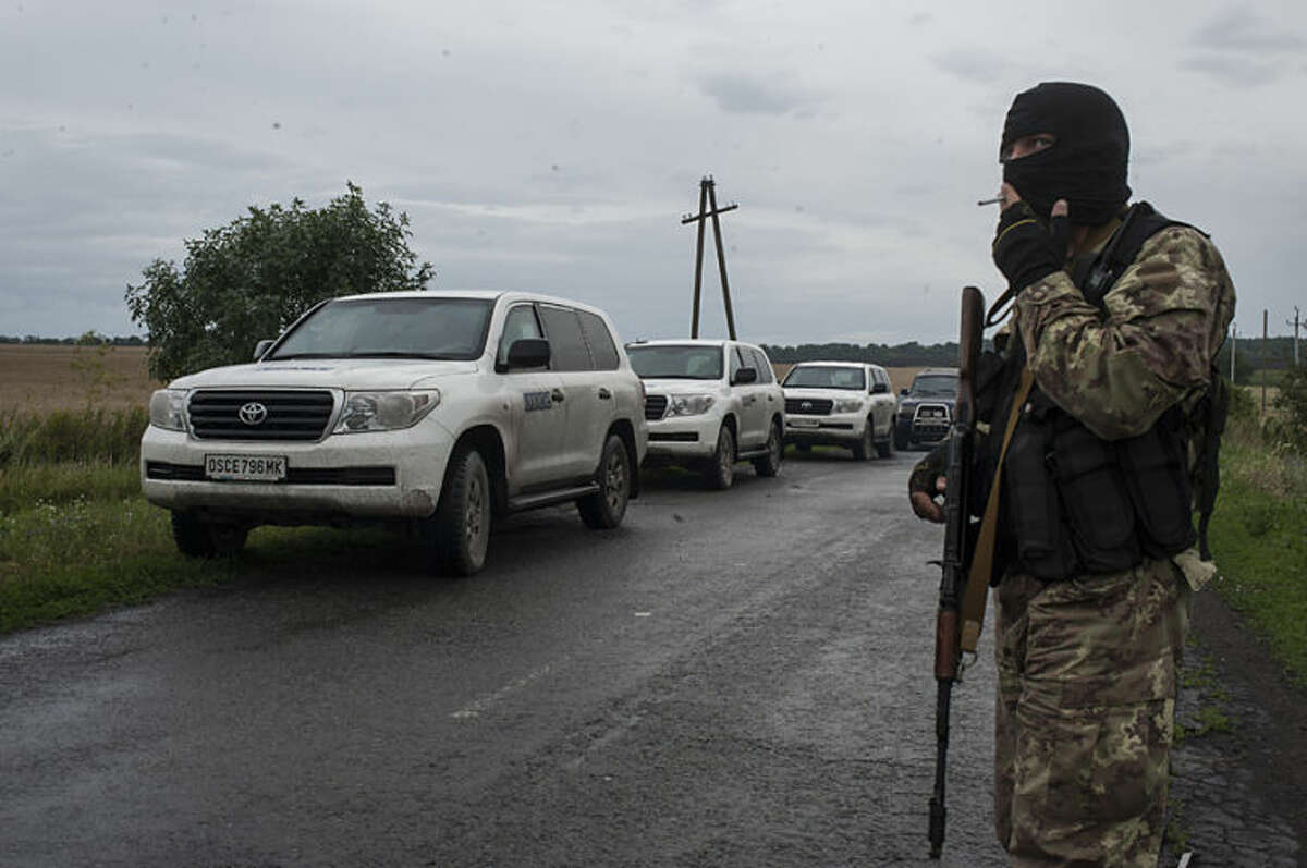 A pro-Russian fighter smokes near the cars of the OSCE (Organization for Security and Co-operation in Europe) after the delegation arrived at the crash site of a Malaysia Airlines jet near the village of Hrabove, eastern Ukraine, Friday, July 18, 2014. Representatives from OSCE and four Ukrainian experts had traveled into rebel-controlled areas to begin an investigation into the downing of the Malaysia Airlines plane and the deaths of all its passengers and crew. (AP Photo/Evgeniy Maloletka)