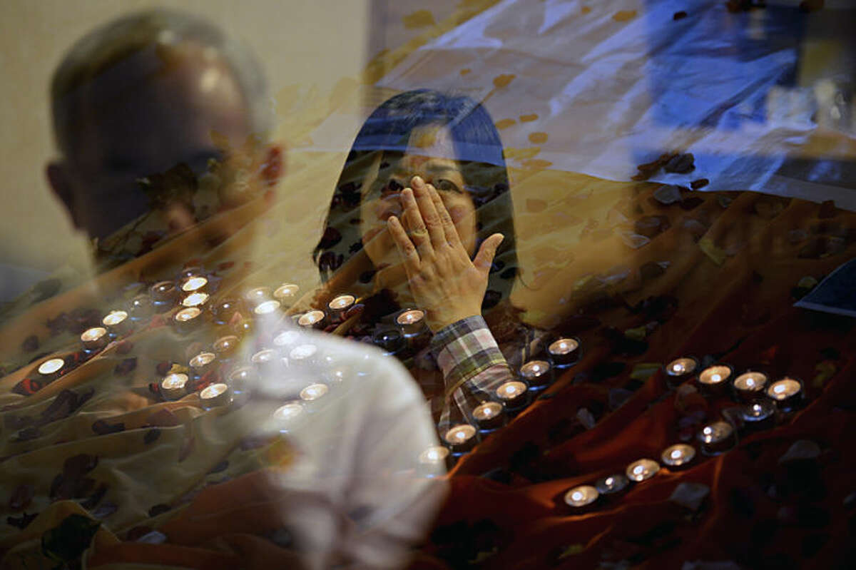 People pray for the victims of Malaysia Airlines Flight 17 at a church outside Kuala Lumpur, Malaysia, Friday, July 18, 2014. The Boeing 777 was carrying 298 people when it was shot down over eastern Ukraine on Thursday in eastern Ukraine, sending shockwaves around the world from Malaysia to the Netherlands. (AP Photo/Joshua Paul)