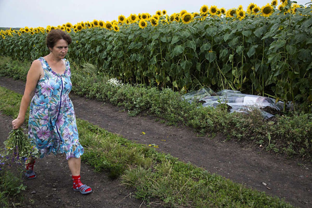 A woman walks past a body covered with a plastic sheet near the site of a crashed Malaysia Airlines passenger plane near the village of Rozsypne, Ukraine, eastern Ukraine Friday, July 18, 2014. Rescue workers, policemen and even off-duty coal miners were combing a sprawling area in eastern Ukraine near the Russian border where the Malaysian plane ended up in burning pieces Thursday, killing all 298 aboard. (AP Photo/Dmitry Lovetsky)