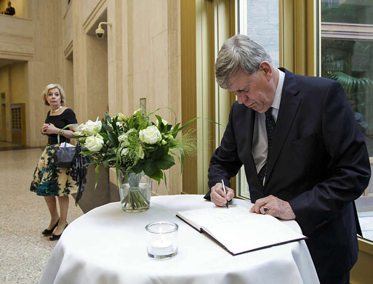 Dutch Justice Minister Ivo Opstelten signs a condolence register at the Ministry of Security and Justice in The Hague, Netherlands, Friday, July 18, 2014. Flags are flying half-staff across the Netherlands as the country mourns at least 173 of its citizens killed when a Malaysia Airlines passenger jet was shot down in eastern Ukraine on Thursday July 17. (AP Photo/Phil Nijhuis)