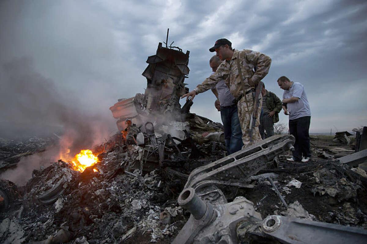 Unas personas inspeccionan el lugar donde cayó el avión de Malaysia Airlines en Hrabove, este de Urania, el jueves 17 de julio de 2014. El avión 295 personas al parecer fue derribado; volaba de Ámsterdam a Kuala Lumpur. (Foto AP/Dmitry Lovetsky)