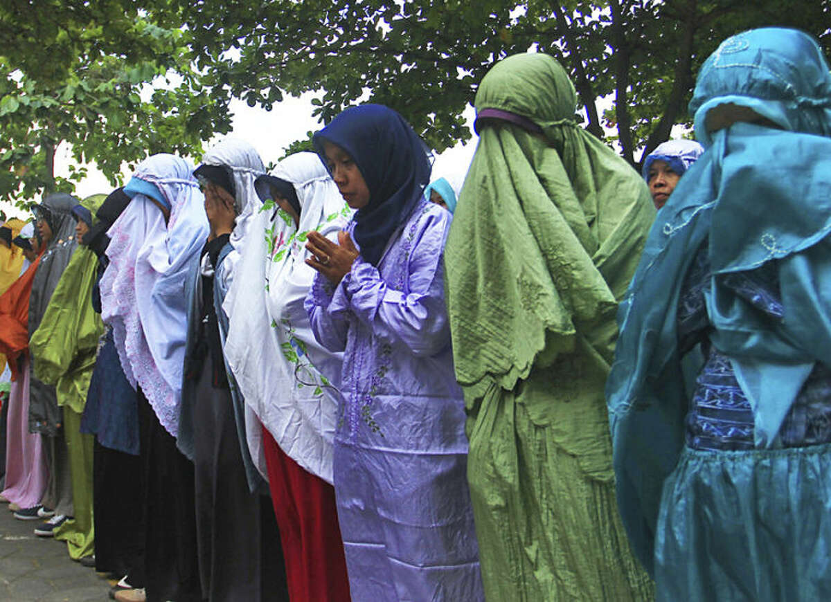 Students of Al Firdaus high school attend a prayer for their guest teacher John Paulissen who was a passenger on board of the crashed Malaysia Airlines flight 17, in Solo, Central Java, Indonesia, Friday, July 18, 2014. The Malaysian jetliner that went down in war-torn Ukraine did not make any distress call, Malaysian Prime Minister Najib Razak said Friday, adding that its flight route had been declared safe by the global civil aviation body. (AP Photo)