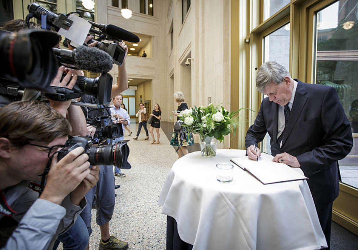 Dutch Justice Minister Ivo Opstelten signs a condolence register at the Ministry of Security and Justice in The Hague, Netherlands, Friday, July 18, 2014. Flags are flying half-staff across the Netherlands as the country mourns at least 173 of its citizens killed when a Malaysia Airlines passenger jet was shot down in eastern Ukraine on Thursday July 17. Opstelten called the Dutch death toll of at least 173, 'an almost unbelievable number. The terrible reality of this disaster is hitting home more and more.' Opstelten told reporters it is critical to establish the exact cause of the tragedy. 'Many of our countrymen and women have died. That is why it is also important that the Netherlands, as part of an international investigative team, can begin research as soon as possible at the location where the aircraft crashed.' (AP Photo/Phil Nijhuis)