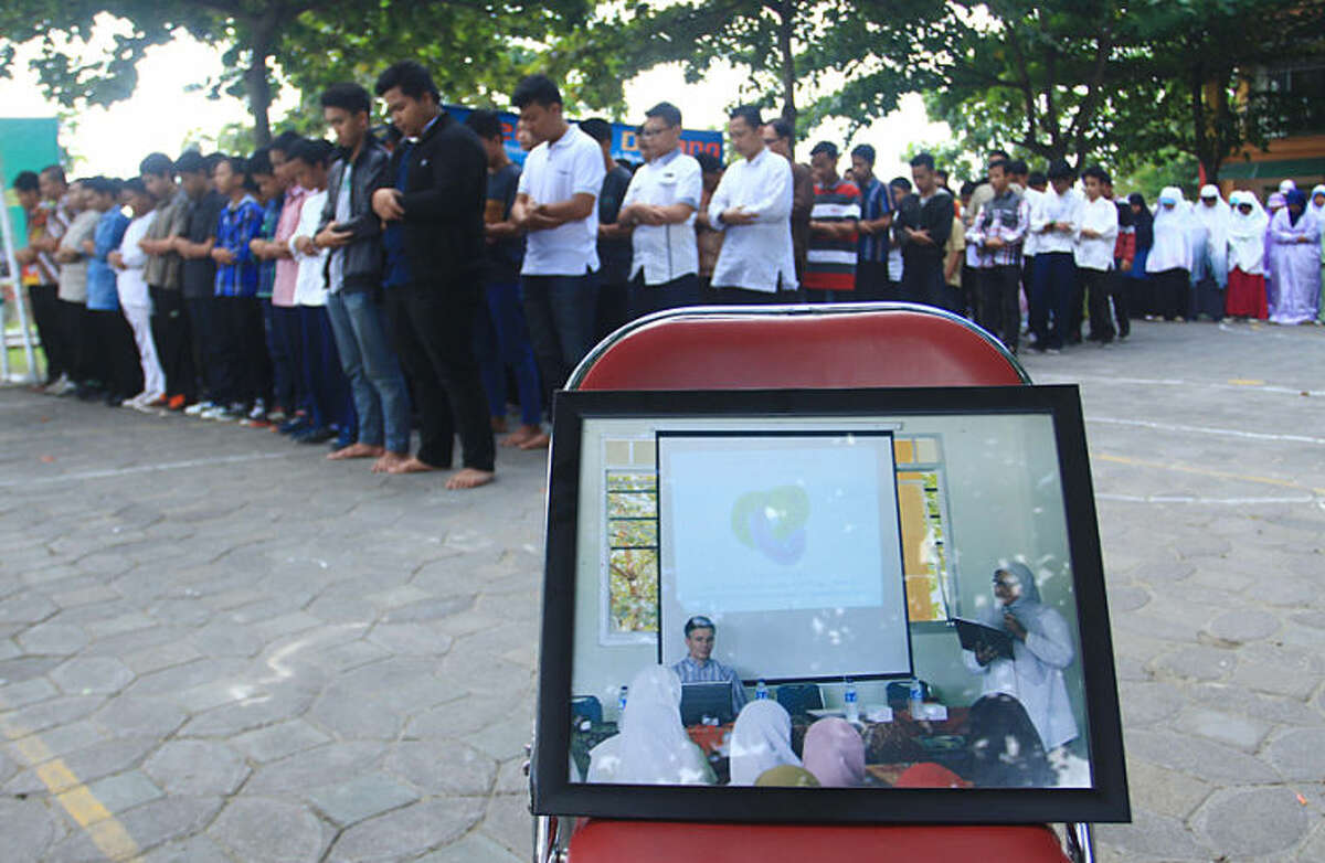 Students of Al Firdaus high school attend a prayer for their guest teacher John Paulissen, showed in the photo in the foreground, who was a passenger on board of the crashed Malaysia Airlines flight 17, in Solo, Central Java, Indonesia, Friday, July 18, 2014. The Malaysian jetliner that went down in war-torn Ukraine did not make any distress call, Malaysian Prime Minister Najib Razak said Friday, adding that its flight route had been declared safe by the global civil aviation body. (AP Photo)