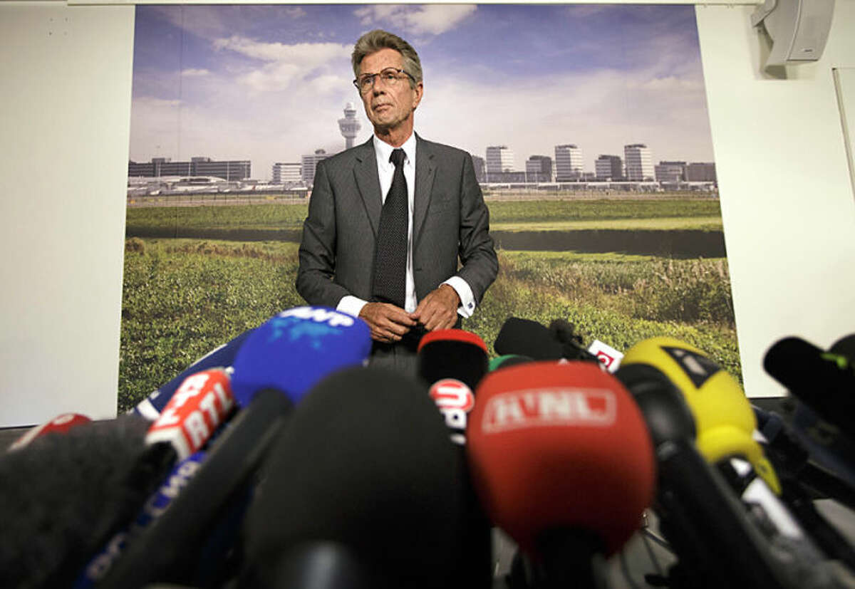 Malaysia Airlines regional vice president Huib Gorter speaks at a crowded press conference at Schiphol airport in Amsterdam, Friday, July 18, 2014. The attack on a Malaysian jetliner Thursday afternoon killed 298 people from nearly a dozen nations, more than half being Dutch, including vacationers, students and a large contingent of scientists heading to an AIDS conference in Australia. Gorter told reporters at Amsterdam's Schiphol Airport the carrier is making an initial payment of $5,000 to families of all victims to cover their immediate costs. (AP Photo/Phil Nijhuis)