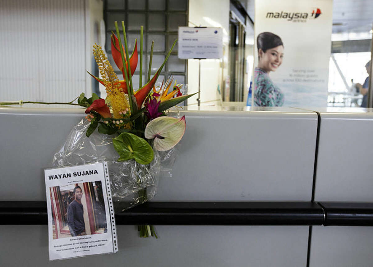 Flowers and a photo of a victim are placed at the desk of Malaysia Airlines, at Schiphol airport in Amsterdam, Friday, July 18, 2014. The attack on a Malaysian jetliner Thursday afternoon killed 298 people from nearly a dozen nations, more than half being Dutch, including vacationers, students and a large contingent of scientists heading to an AIDS conference in Australia. (AP Photo/Phil Nijhuis)