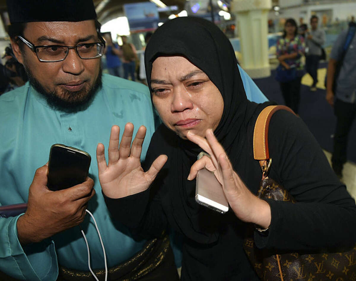 Relatives of passengers aboard the Malaysia Airlines Flight 17 react as they arrive at Kuala Lumpur International Airport in Sepang, Malaysia, Friday, July 18, 2014. The Malaysia Airlines jetliner that went down in war-torn Ukraine did not make any distress call, Malaysia's prime minister said Friday, adding that its flight route had been declared safe by the global civil aviation body. (AP Photo) MALAYSIA OUT