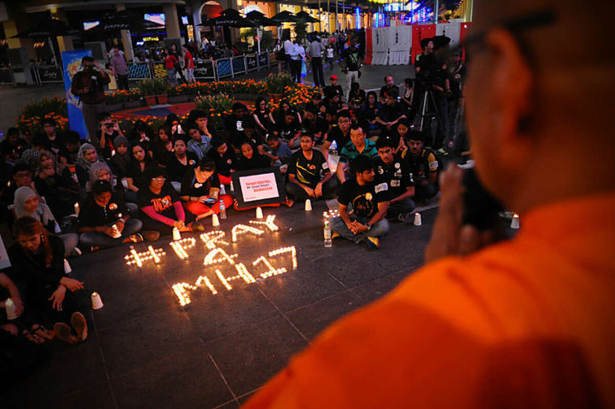 A Buddhist monk leads the prayers during a candlelight vigil for the victims of Malaysia Airlines Flight 17 at a shopping mall in Petaling Jaya near Kuala Lumpur, Malaysia, Friday, July 18, 2014. The Malaysia Airlines jetliner was carrying 298 people when it was shot down over eastern Ukraine on Thursday in eastern Ukraine, sending shockwaves around the world from Malaysia to the Netherlands. (AP Photo/Joshua Paul)