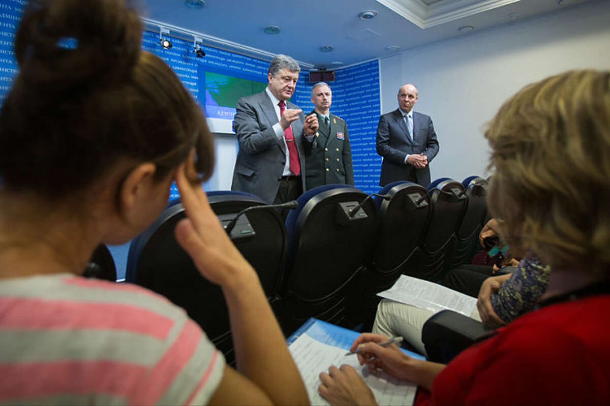 Ukrainian President Petro Poroshenko meets with mothers and wives of Ukrainian soldiers on duty in eastern Ukraine, in Kiev, Ukraine, Thursday, July 17, 2014. Ukrainian President Petro Poroshenko called the downing of a Malaysia Airlines passenger plane an act of terrorism and called for an international investigation into the crash. He insisted that his forces did not shoot down the plane. (AP Photo/Presidential Press Service, Mykhailo Markiv, Pool)