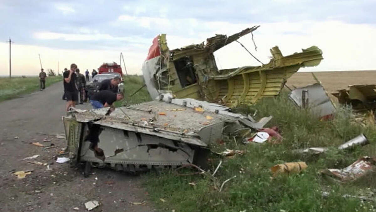 In this image taken from video, Thursday July 17, 2014, showing part of the wreckage of a passenger plane carrying 295 people after it was shot down Thursday as it flew over Ukraine, near the village of Hrabove, in eastern Ukraine. Malaysia Airlines tweeted that it lost contact with one of its flights as it was traveling from Amsterdam to Kuala Lumpur over Ukrainian airspace.(AP Photo / Channel 1) RUSSIA OUT - TV OUT