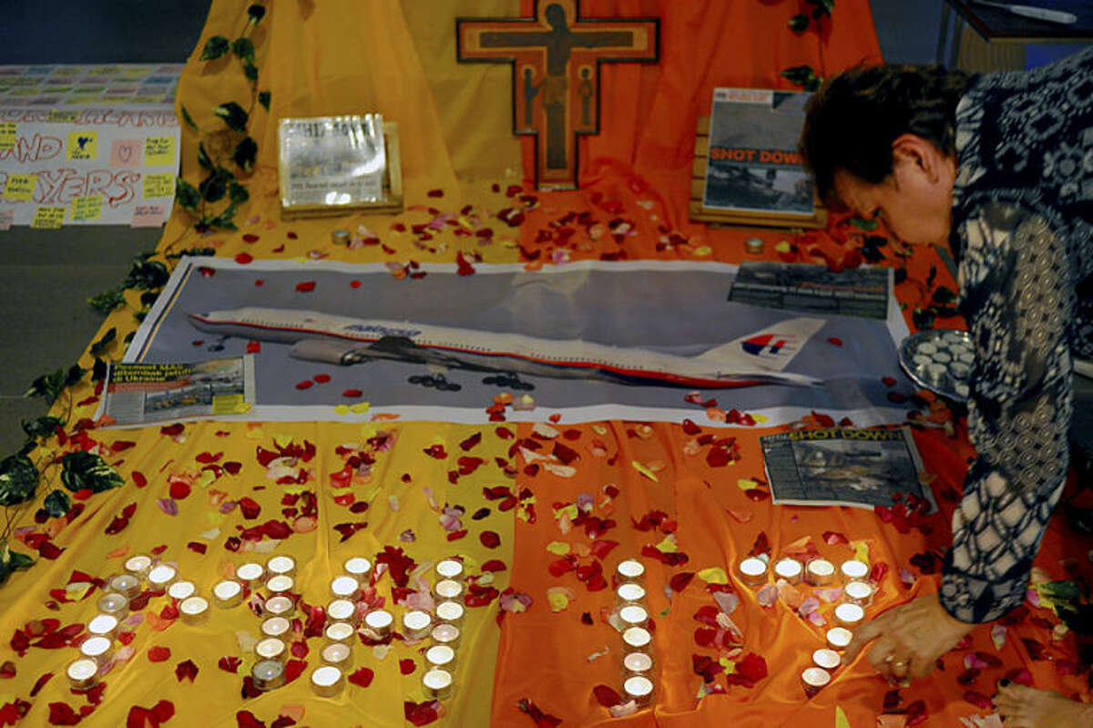 Candles are placed for a prayer for victims of the Malaysia Airlines Flight 17 at a church outside Kuala Lumpur, Malaysia, Friday, July 18, 2014. The Malaysia Airlines jetliner was carrying 298 people when it was shot down over eastern Ukraine on Thursday in eastern Ukraine, sending shockwaves around the world from Malaysia to the Netherlands. (AP Photo/Joshua Paul)