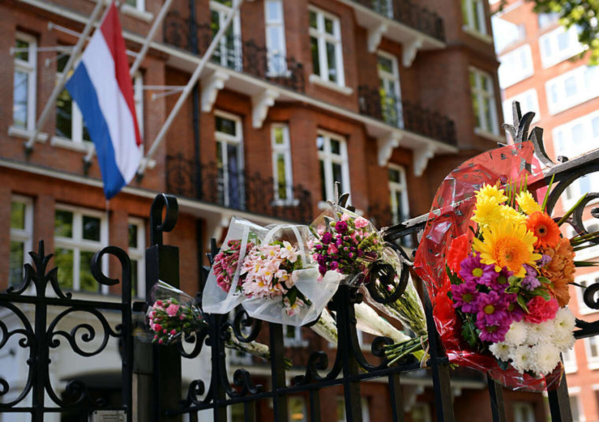 The Netherlands flag flies at half staff as flowers are laid outside the The Netherlands' Embassy in London, Friday July 18, 2014 to remember the passengers who were killed on Malaysian Flight MH17, which crashed in Ukraine Thursday as it travelled from Amsterdam to Kuala Lumpur. All 298 people onboard the plane died with more than half of them being Dutch nationals. (AP Photo/Stefan Rousseau/PA)
