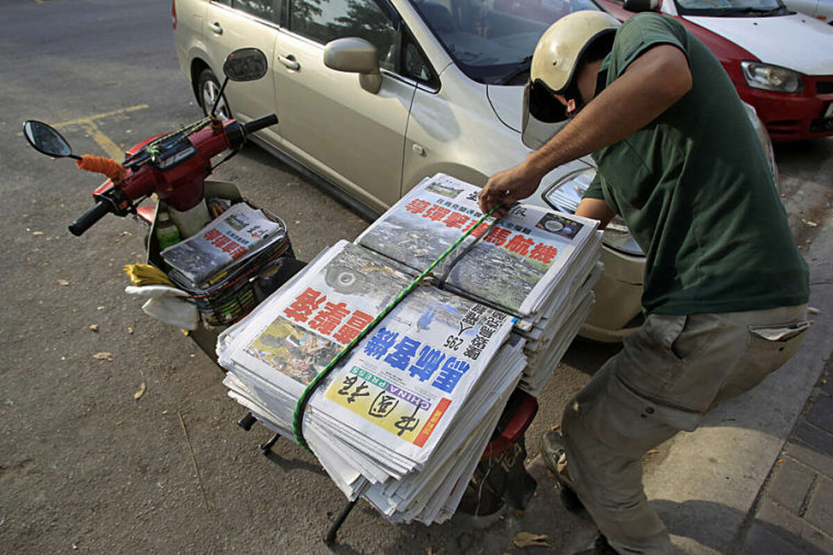 A newspaper delivery man prepares to unload Chinese newspapers carrying headline stories and pictures of Thursday's Malaysia Airlines plane shot down, in Shah Alam, outside Kuala Lumpur, Malaysia, Friday, July 18, 2014. Malaysia Airlines has increased the death toll from Flight 17 that was shot down over war-torn eastern Ukraine on Thursday to 298 from 295, saying that three infants had not been included in the original list. (AP Photo/Lai Seng Sin)