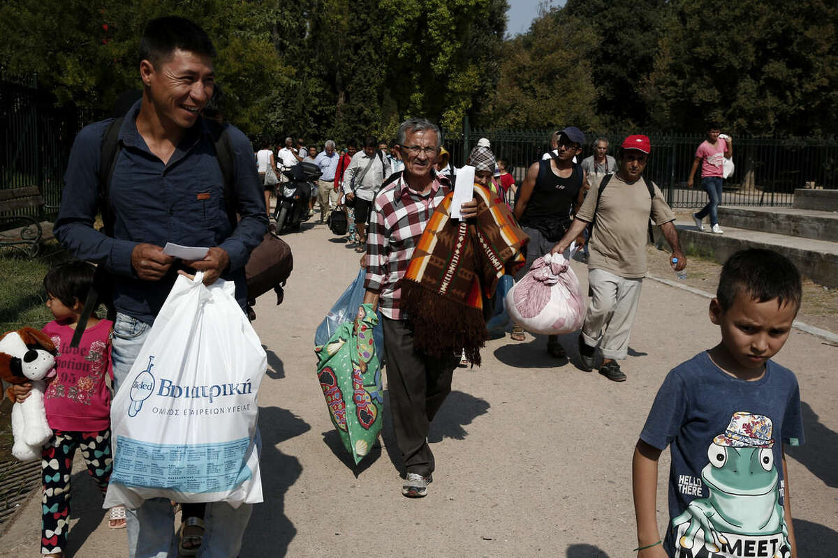 Migrants carry their belongings as they walk to an organized camp which has been set up by the Greek state a few miles off the centre of Athens, Sunday, Aug. 16, 2015. Greek authorities say they have started resettling migrants living in tents in a park in the capital Athens, but many are wary of such a move and have moved to directions unknown thus far. (AP Photo/Yorgos Karahalis)