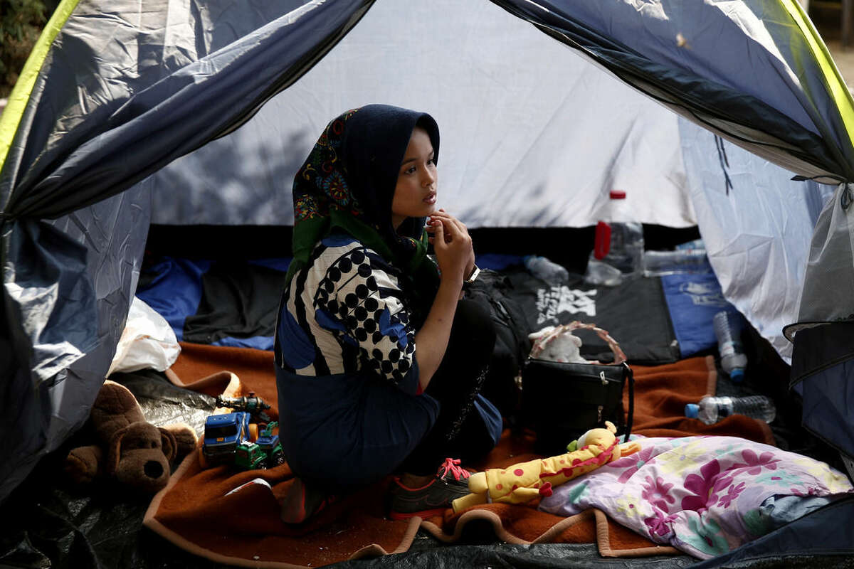 A migrant sits inside a tent at a park as she waits to be transferred along with other migrants to a organized camp which has been set up by the Greek state a few miles from the centre of Athens, Sunday, Aug. 16, 2015. Greek authorities say they have started resettling migrants living in tents in a park in the capital Athens, but many are wary of such a move and have moved to directions unknown thus far. (AP Photo/Yorgos Karahalis)