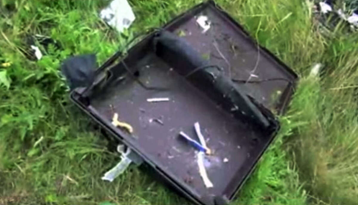 This image taken from video, Thursday July 17, 2014, shows a suitcase found in the wreckage of a passenger plane carrying 295 people after it was shot down Thursday as it flew over Ukraine, near the village of Hrabove, in eastern Ukraine. Malaysia Airlines tweeted that it lost contact with one of its flights as it was traveling from Amsterdam to Kuala Lumpur over Ukrainian airspace. (AP Photo/Channel 1) RUSSIA OUT - TV OUT