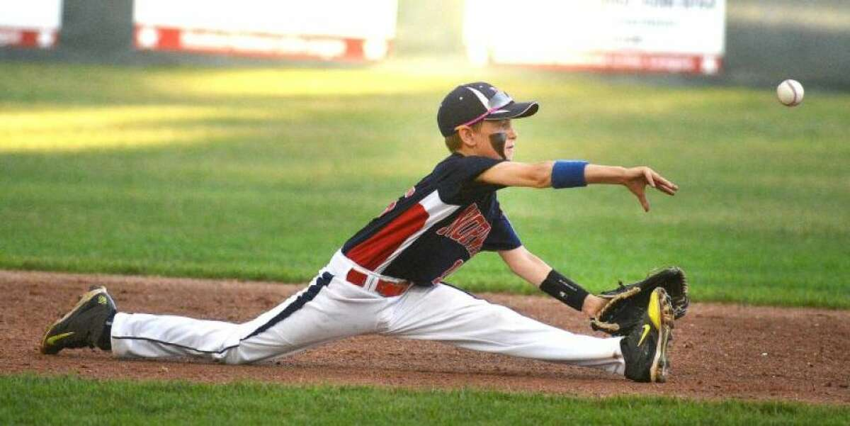 Hour Photo/Alex von Kleydorff. Norwalks #15 Alistair Morin makes the throw to first base for the play