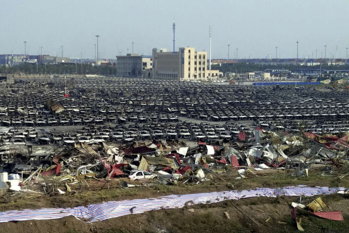 Charred remains of new cars are seen in a parking lot near the site of the chemical explosion at a warehouse in northeastern China's Tianjin municipality, Monday, Aug. 17, 2015. The blasts on last Wednesday night originated at a warehouse for hazardous material, where 700 tons of sodium cyanide - a toxic chemical that can form combustible substances on contact with water - were being stored in amounts that violated safety rules. That has prompted contamination fears and a major cleanup of a 3-kilometer (1.8-mile) -radius, cordoned-off area in this Chinese port city southeast of Beijing. (Chinatopix via AP) CHINA OUT