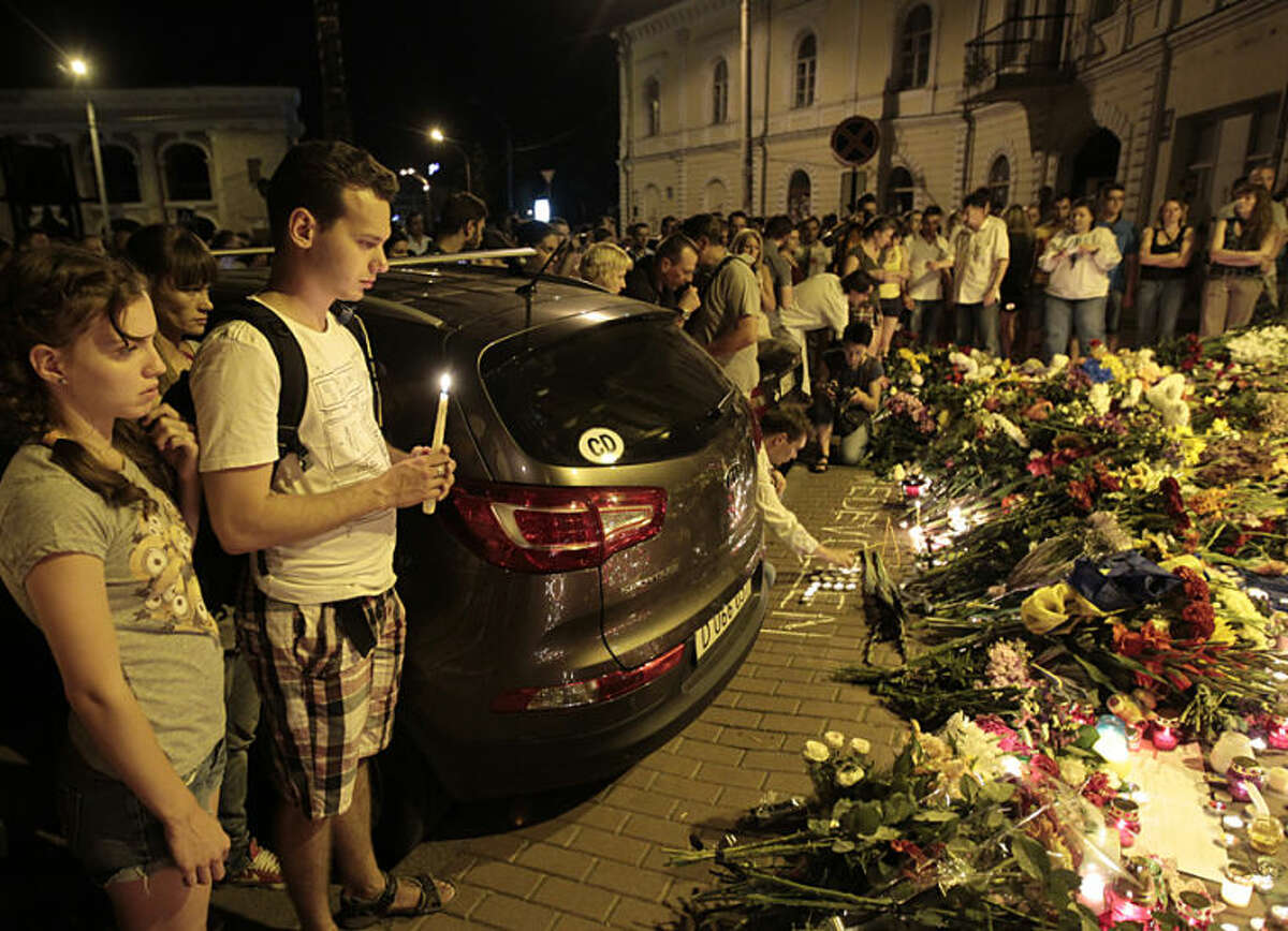 People stand near flower tributes placed outside the Dutch embassy to commemorate victims of Malaysia Airlines plane crash in Kiev, Ukraine, Thursday, July 17, 2014. A Malaysian Airlines passenger jet was shot down in eastern Ukraine on Thursday, and both the Ukrainian government and pro-Russian rebels blamed one another for the attack.(AP Photo/Sergei Chuzavkov)