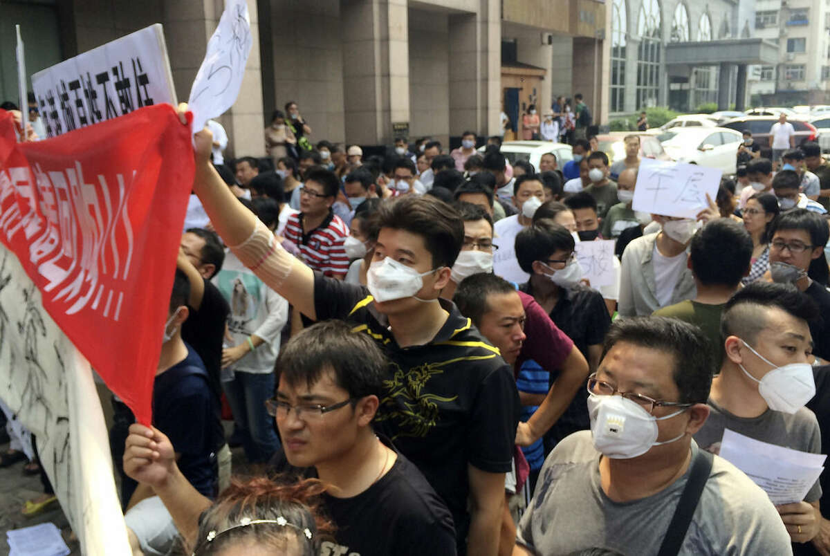 Residents, some wearing masks, hold banners and placards as they stage a protest outside a hotel where officials held daily media conferences in northeastern China's Tianjin municipality Monday, Aug. 17, 2015. About a hundred people whose residences were damaged in the massive Tianjin blasts gathered Monday for a protest to demand compensation from the government. (AP Photo/Paul Traynor)