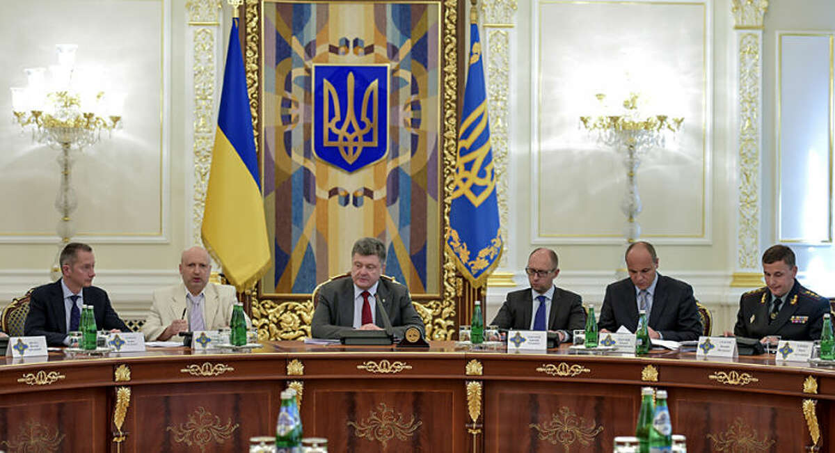 Ukrainian President Petro Poroshenko, third left, chairs a Security Council meeting in Kiev, Ukraine, Thursday, July 17, 2014. Ukrainian President Petro Poroshenko called the downing of a Malaysia Airlines passenger plane an act of terrorism and called for an international investigation into the crash. Poroshenko insisted that his forces did not shoot down the plane. From right, Ukrainian Defense MInister Valery Heletey, Head of the Security Council Andriy Parubiy, Prime Minister Arseniy Yatsenyuk, Petro Poroshenko, parliament speaker Oleksandr Turchynov. (AP Photo/Presidential Press Service, Mykola Lazarenko)