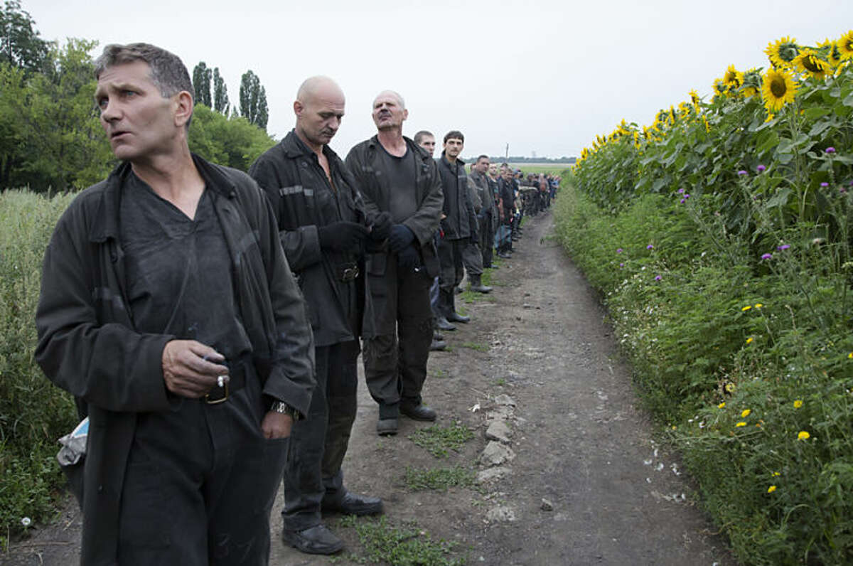 Ukrainian coal miners prepare to search the site of a crashed Malaysia Airlines passenger plane near the village of Rozsypne, Ukraine, eastern Ukraine Friday, July 18, 2014. Rescue workers, policemen and even off-duty coal miners were combing a sprawling area in eastern Ukraine near the Russian border where the Malaysian plane ended up in burning pieces Thursday, killing all 298 aboard. (AP Photo/Dmitry Lovetsky)