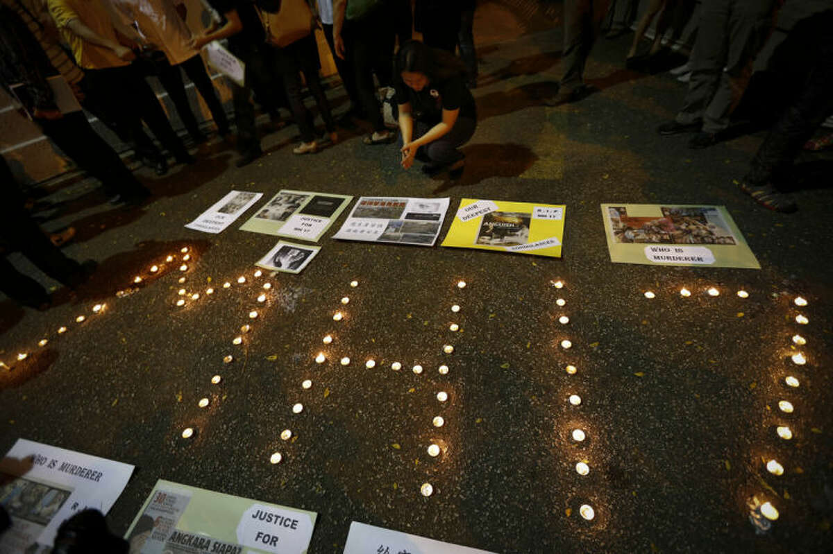 """A woman looks at newspaper cuttings at a candlelight vigil for the victims of Malaysia Airlines Flight 17 in Kuala Lumpur, Malaysia, Saturday, July 19, 2014. Malaysian Transport Minister Liow Tiong Lai said the country is """"deeply concerned"""" that the site in Ukraine where the Malaysia Airlines jetliner was shot down with 298 people onboard """"has not been properly secured. (AP Photo/Vincent Thian)"""