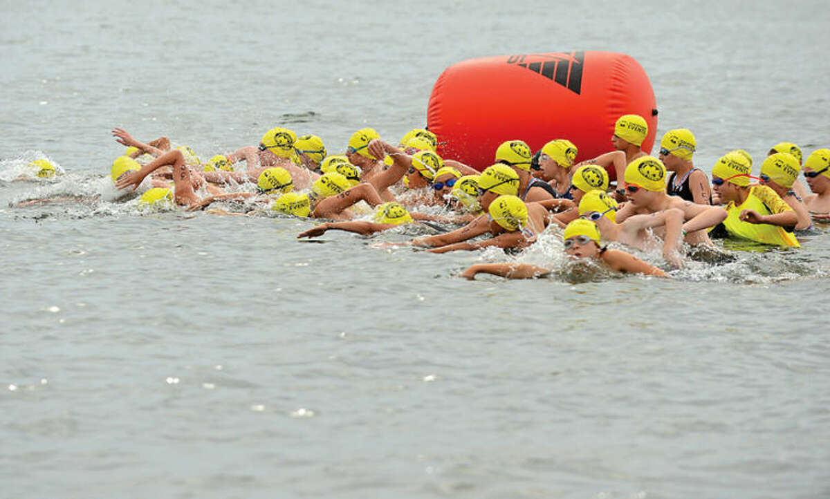 Hour photo / Erik Trautmann Swimmers compete in the 11-14 year old division of the 2014 Mini Mossman Youth Triathlon at Calf Pasture Beach Saturday.