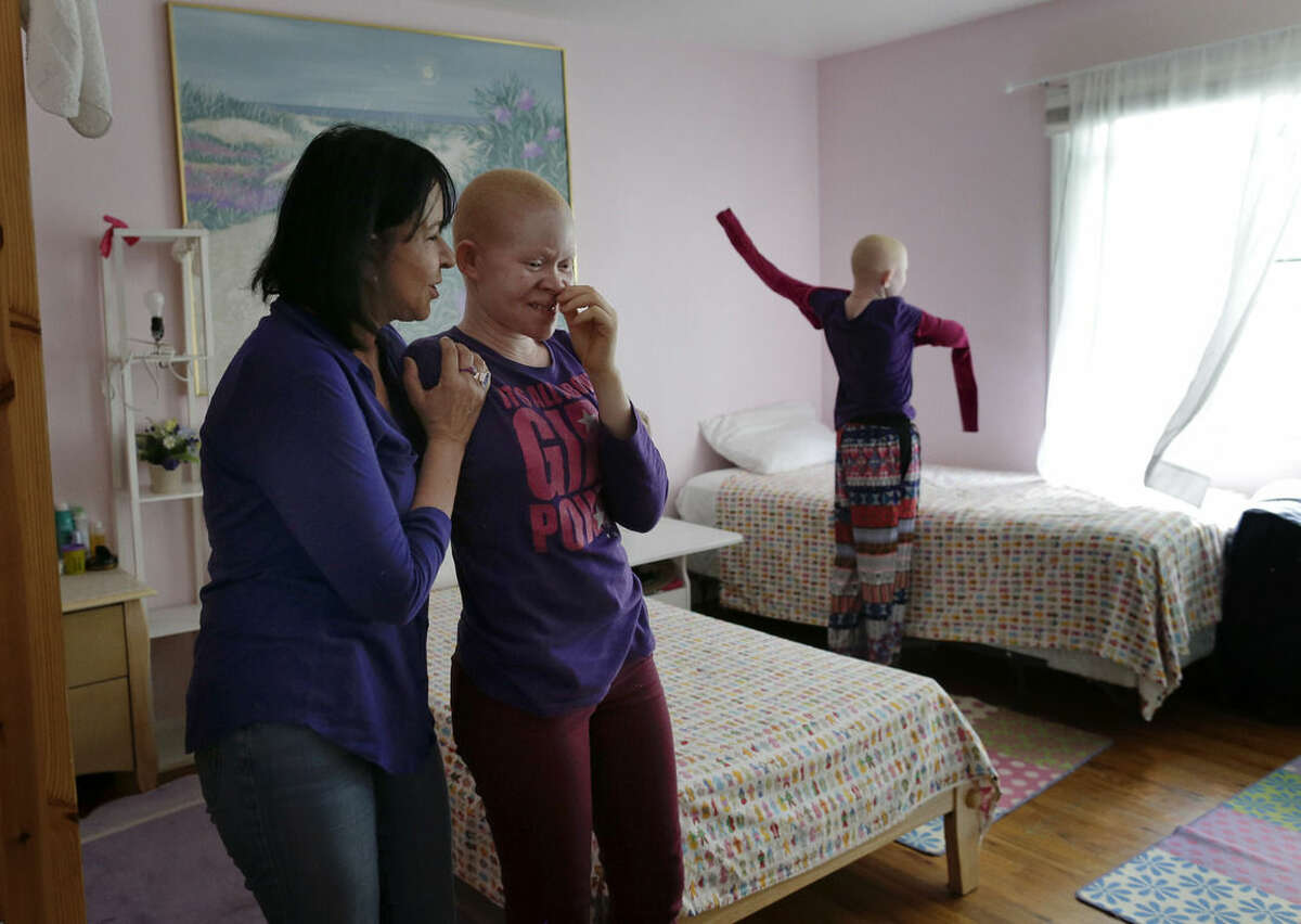 Elissa Montanati, left, founder and director of the Global Medical Relief Fund tries to encourage Kabula Masanja to sing as Pendo Noni tries on a new shirt in New York on Wednesday, July 1, 2015. People with the genetic condition of albinism, characterized by a lack of pigment, are often referred to in Tanzania as ghosts, or zero zero, which in Swahili signifies someone who is less than human. (AP Photo/Julie Jacobson)