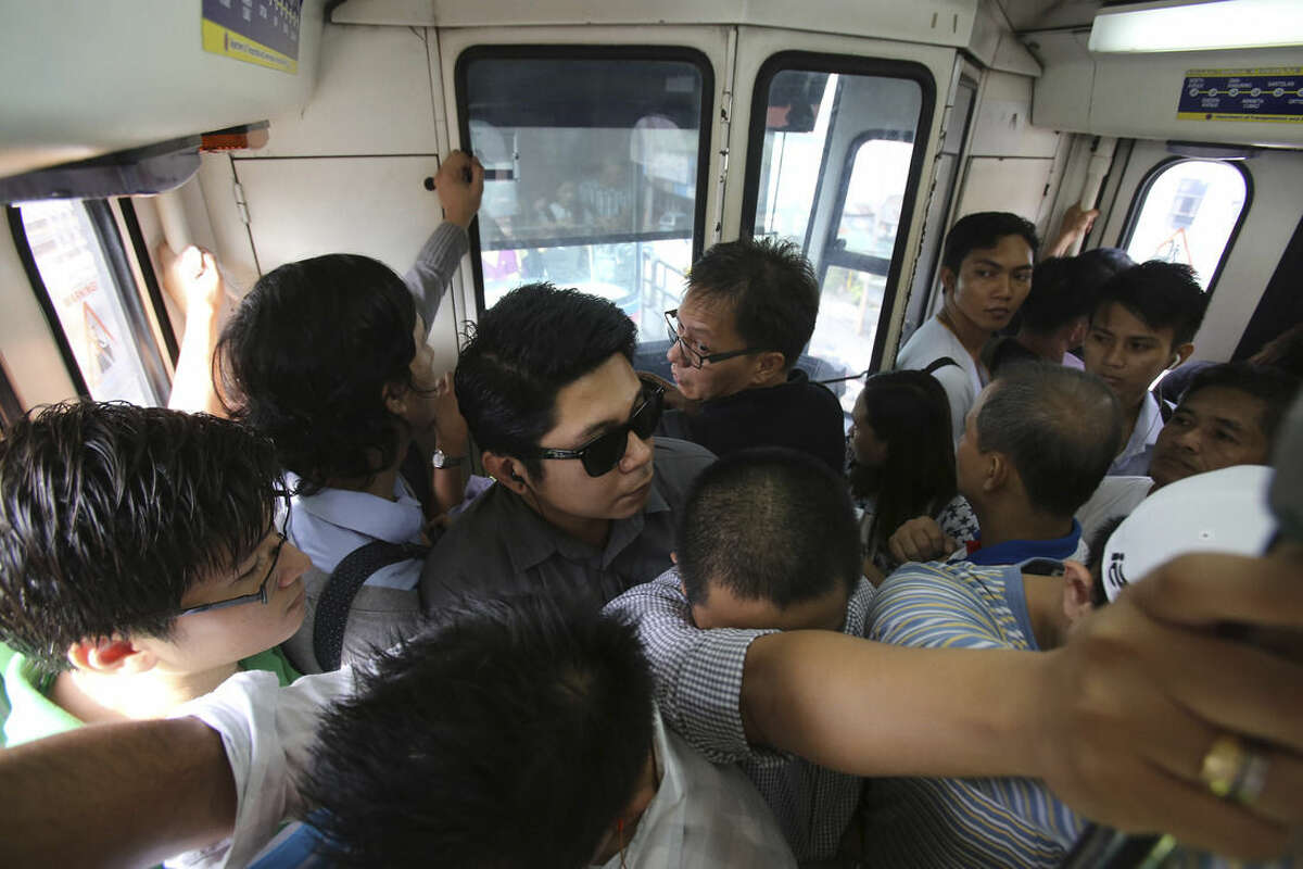 In this Tuesday, Aug. 11, 2015 photo, Filipino passengers ride a crowded train of the Manila Metro Rail Transit System during rush hour in the financial district of Makati, south of Manila, Philippines. Manila and other cities are choked with construction sites for office and apartment towers. But spending on roads, railways and other unglamorous but essential infrastructure collapsed after the 1997 financial crisis and has yet to recover. (AP Photo/Aaron Favila)