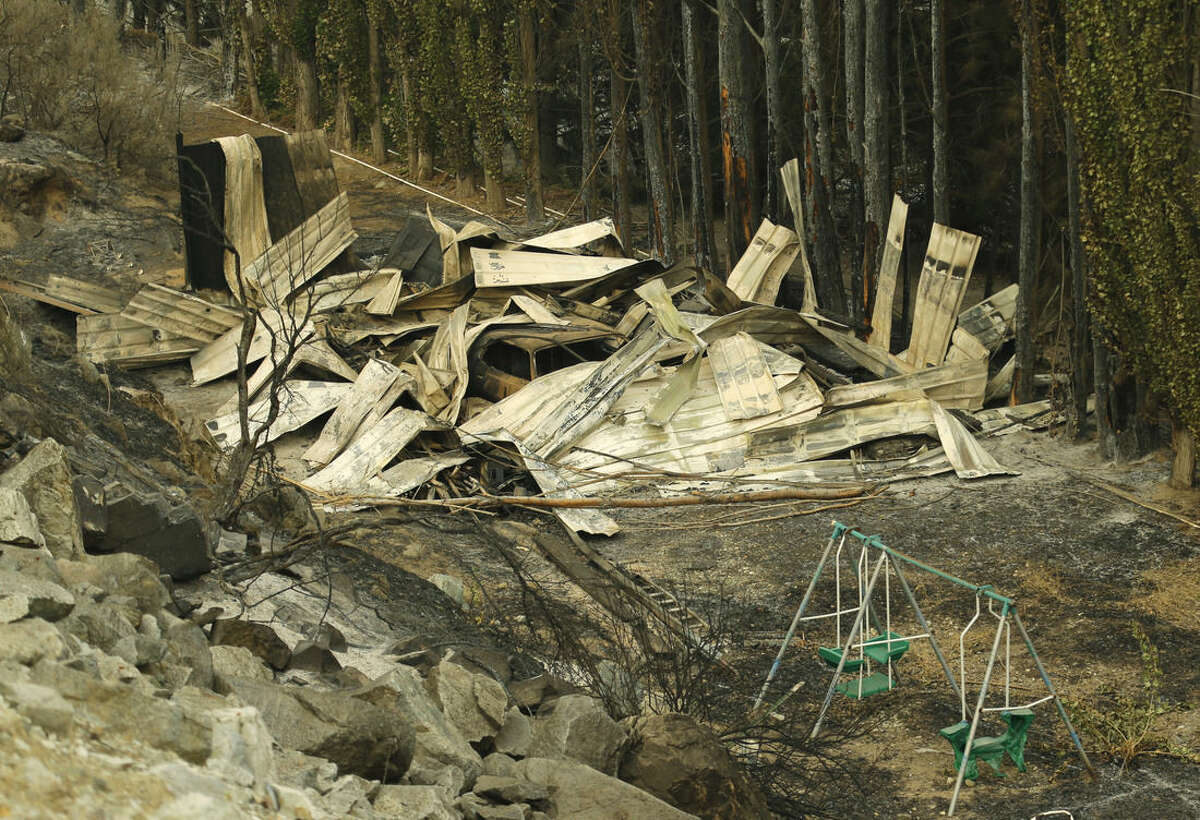 A partially melted swing set sits next to a burned structure along State Route Alt. 97 highway Monday, Aug. 17, 2015, outside of Chelan, Wash. The blazes near Chelan, about 180 miles east of Seattle, are burning through grass, brush and timber, fire spokeswoman Janet Pearce said. (AP Photo/Ted S. Warren)