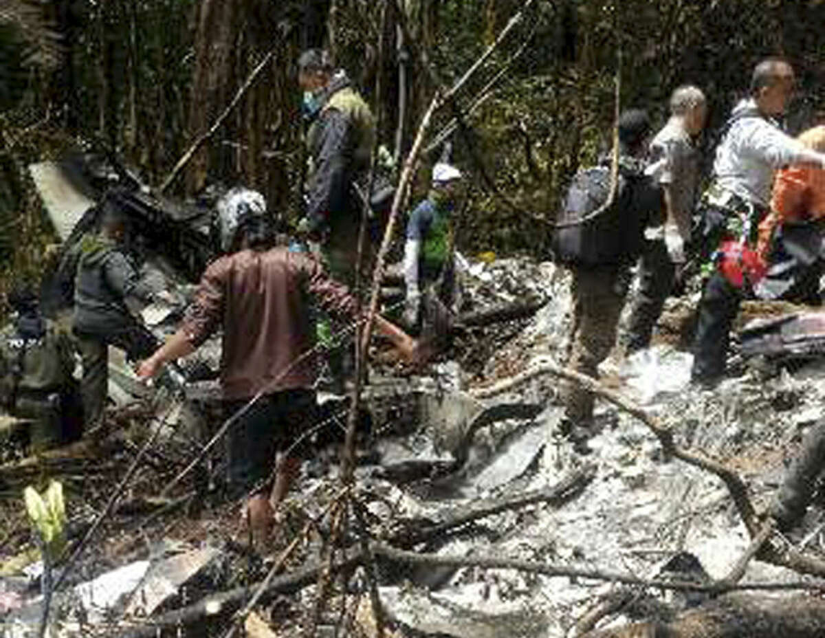 Officials and rescue workers gather by plane wreckage strewn across dense terrain in a remote area of Pegunungan Bintang, Papua province, Indonesia, Tuesday, Aug. 18, 2015. The Trigana Air Service plane that went missing two days ago was destroyed when it slammed into a mountain, killing all 54 people on board, the country's top rescue official said. (AP Photo)