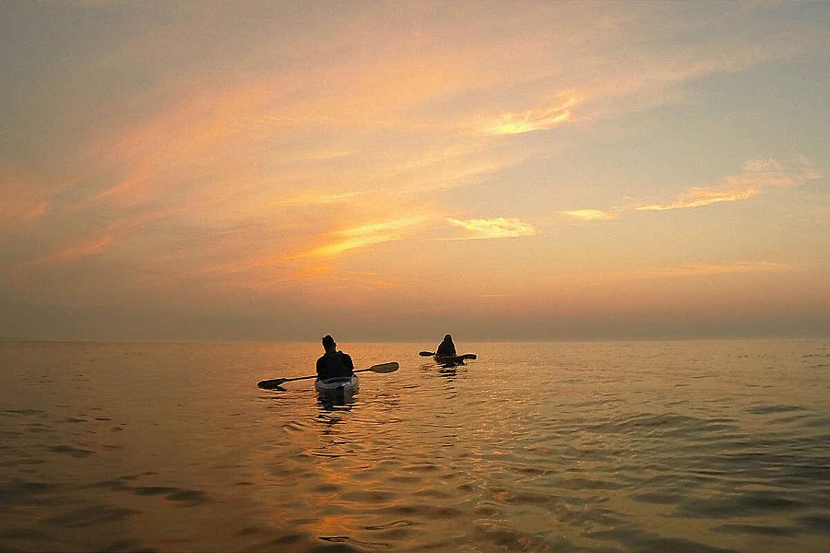 Kayakers paddle on Lake Michigan at sunrise, Monday, Aug. 17, 2015, in Cedar Grove, Wis. (AP Photo/Julio Cortez)