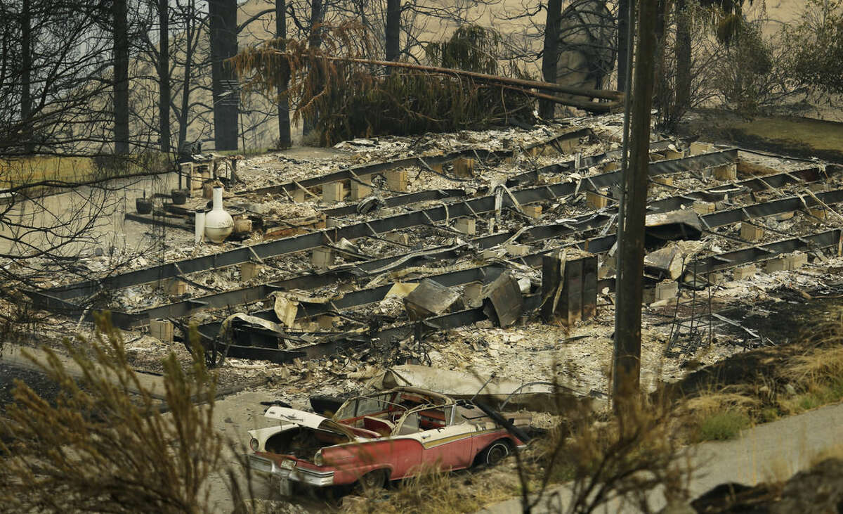 Remains from a burned structure sit along State Route Alt. 97 highway Monday, Aug. 17, 2015, outside of Chelan, Wash. Big wildfires threatened the Lake Chelan resort region of central Washington on Monday after driving away tourists, destroying a warehouse filled with nearly 2 million pounds of apples and forcing thousands of residents to flee. (AP Photo/Ted S. Warren)