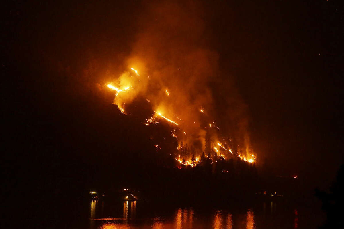 Timber burns in the First Creek fire near lakeside structures on the western shore of Lake Chelan late Monday, Aug. 17, 2015, near Chelan, Wash. Big wildfires threatened the Lake Chelan resort region of central Washington on Monday after driving away tourists, destroying a warehouse filled with nearly 2 million pounds of apples and forcing thousands of residents to flee. (AP Photo/Ted S. Warren)