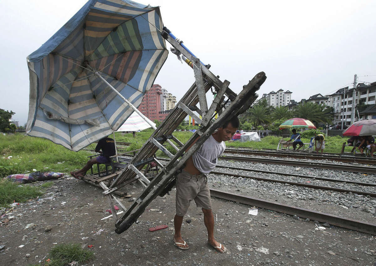 In this Wednesday, Aug. 12, 2015 photo, Filipino Ramil Santos parks his metal-wheeled cart with benches fashioned from scrap wood as he waits for passengers along the railway in Manila, Philippines. Manila and other cities are choked with construction sites for office and apartment towers. But spending on roads, railways and other unglamorous but essential infrastructure collapsed after the 1997 financial crisis and has yet to recover. (AP Photo/Aaron Favila)